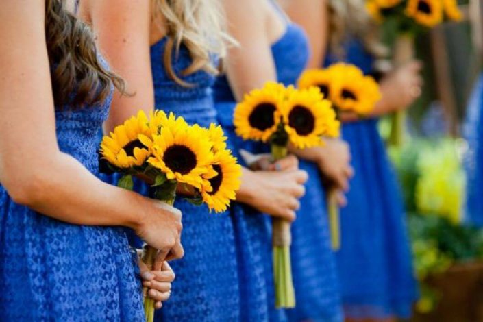 Bridesmaids carrying sunflower pugettes